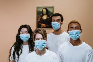 Een foto met vier mensen met een mondkapje voor.